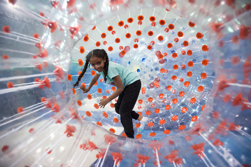 "Kaylynn Miller, 8, participates in a hamster ball race while the Broomfield High School JAM was opened to the public early Saturday evening. JAM, a free after-prom party, provides a safe, drug-free environment for juniors and seniors. <br /> More photos:  <a href=""http://www.dailycamera.com"">http://www.dailycamera.com</a><br /> Autumn Parry/Staff Photographer<br /> April 30, 2016"