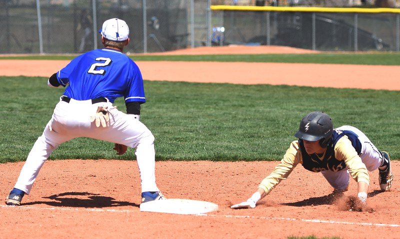 Legacy's Joshua Kelnhofer dives back to first base ahead of a pick-off throw during the baseball game between Broomfield and Legacy on Saturday, April 28, at Legacy High School in Broomfield.