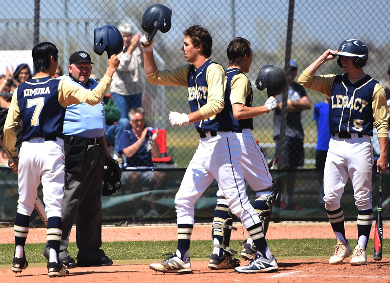 The Legacy players celebrate at home plate after Ross Smith's two-run home run in the second inning of the baseball game between Broomfield and Legacy on Saturday, April 28, at Legacy High School in Broomfield.