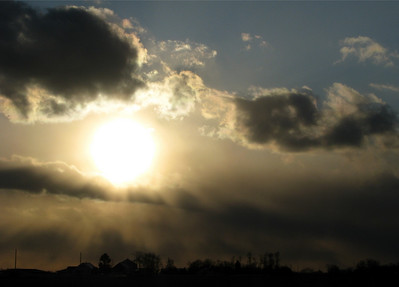 The sun shining through some snow clouds near Columbus Ohio on a particularly cold day.