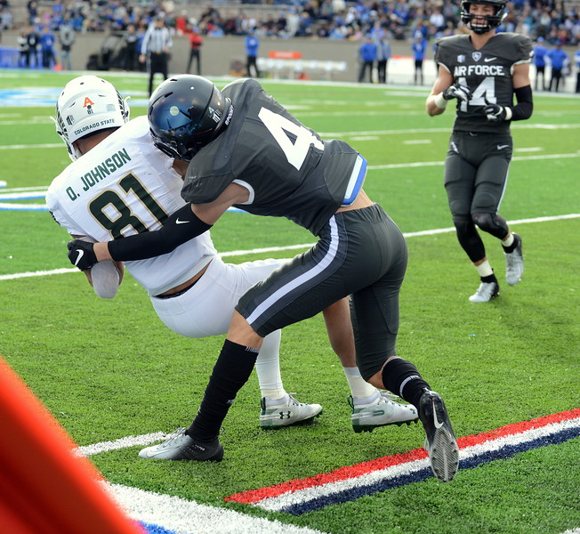 Colorado State wideout Bisi Johnson is tackled on the sideline by Air Force's Milton Bugg III after picking up a first down during Thursday's game at Air Force. (Mike Brohard/Loveland Reporter-Herald).