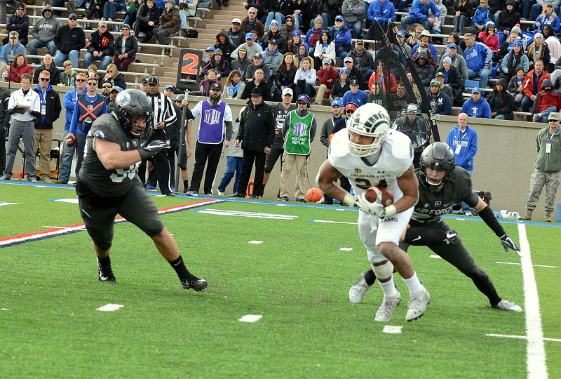Colorado State running back Izzy Matthews breaks through the tackle of Air Force's Garrett Kauppila during Thursday's game at Air Force. (Mike Brohard/Loveland Reporter-Herald).