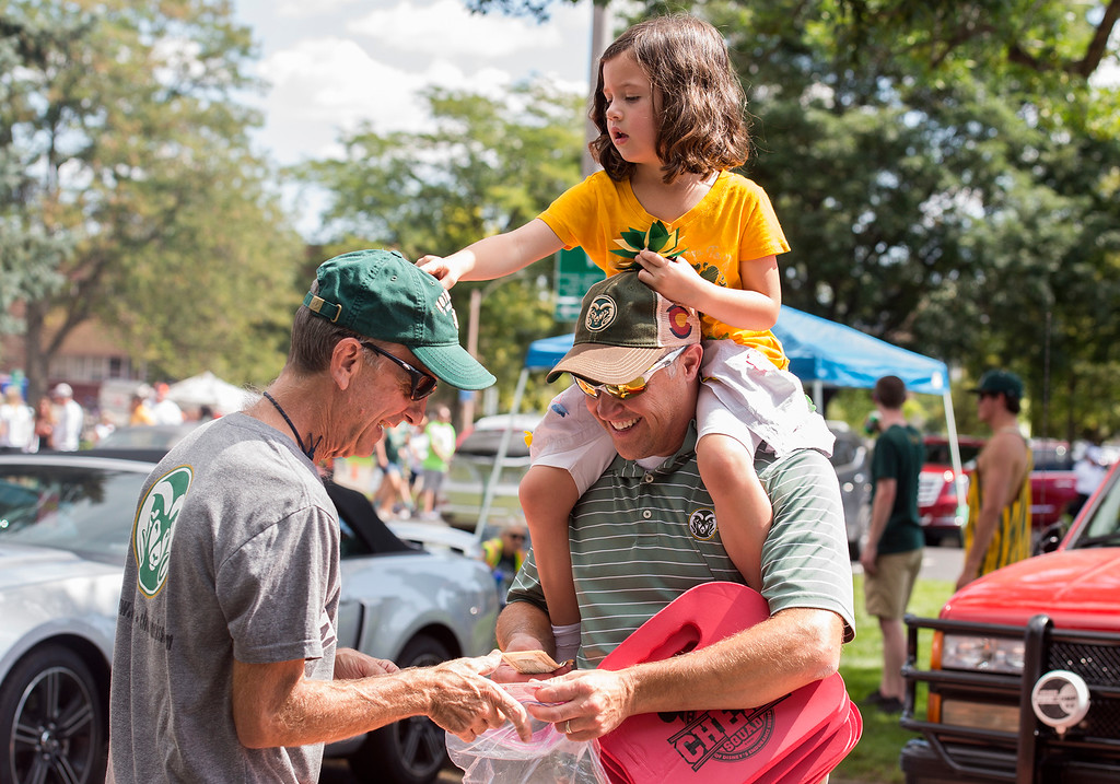. Ken Jurjovec, right, buys a ticket at face value from another CSU Ram fan, left, as Piper Kurjovec, 4, rides his shoulders Saturday morning August 26, 2017 prior to the Ram\'s inaugural football game at the new on-campus stadium in Fort Collins. (Michael Brian/For the Reporter-Herald)