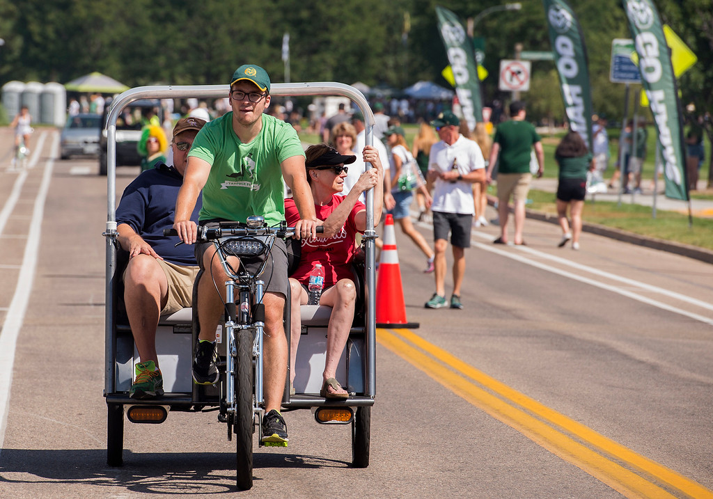 . A new sight at CSU football games, Kevin Kruglet with Tadpole Pedicabs takes alumns John and Katy Harding, from Colorado Springs, down Meridian Avenue to the stadium Saturday morning August 26, 2017 prior to the Ram\'s inaugural football game at the new facility in Fort Collins. (Michael Brian/For the Reporter-Herald)