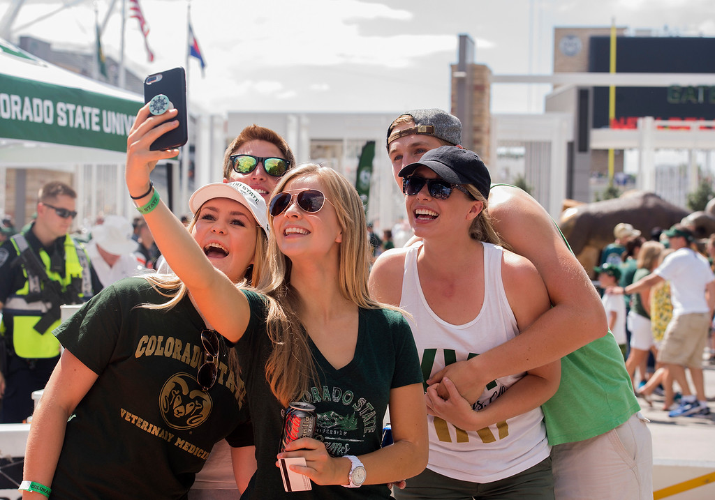 . From left, Colorado State students Kelsey Dobesh, Dustin Gusterry, Emily Reynolds, Parker Lewis, and Jenna Schuster take a groupie with the CSU on-campus stadium in the background Saturday morning August 26, 2017 prior to the Ram\'s inaugural football game at the new facility in Fort Collins. (Michael Brian/For the Reporter-Herald)