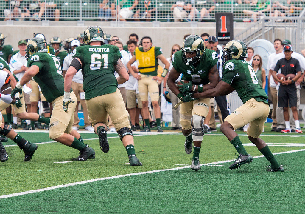 . Colorado State running back Marvin Kinsey Jr. (5), center, takes an option handoff from wide receiver Detrich Clark (8), right, against Oregon State Saturday afternoon August 26, 2017 during the Ram\'s inaugural football game at the new on-campus stadium in Fort Collins. The Rams prevailed, 58-27. (Michael Brian/For the Reporter-Herald)