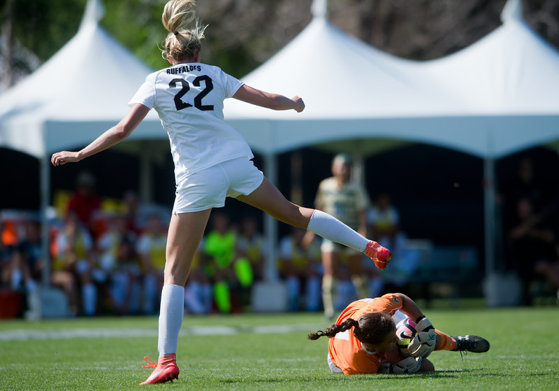 "CU's Taylor Kornieck jumps over CSU's goalkeeper, Sydney Hall, as Hall saves the ball  during the soccer game at Prentup Field at CU Boulder on Sunday. CU Boulder defeated CSU 2-1.<br /> More photos:  <a href=""http://www.buffzone.com"">http://www.buffzone.com</a><br /> (Autumn Parry/Staff Photographer)<br /> August 21, 2016"