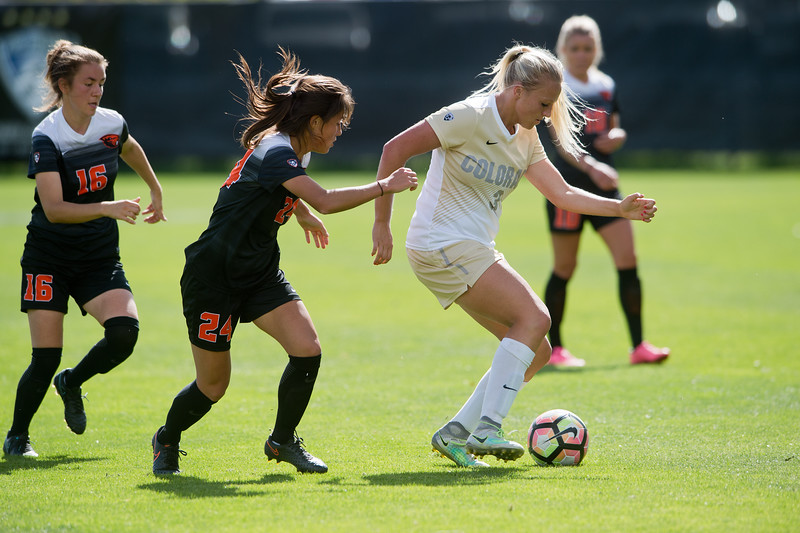"CU's Emily Bruder navigates the ball past Oregon State's Annie Govig and Sabrina Santarossa during the game in Prentup Field at CU Boulder on Sunday. CU defeated Oregon State 3-0. <br /> More photos:  <a href=""http://www.buffzone.com"">http://www.buffzone.com</a><br /> (Autumn Parry/Staff Photographer)<br /> October 9, 2016"