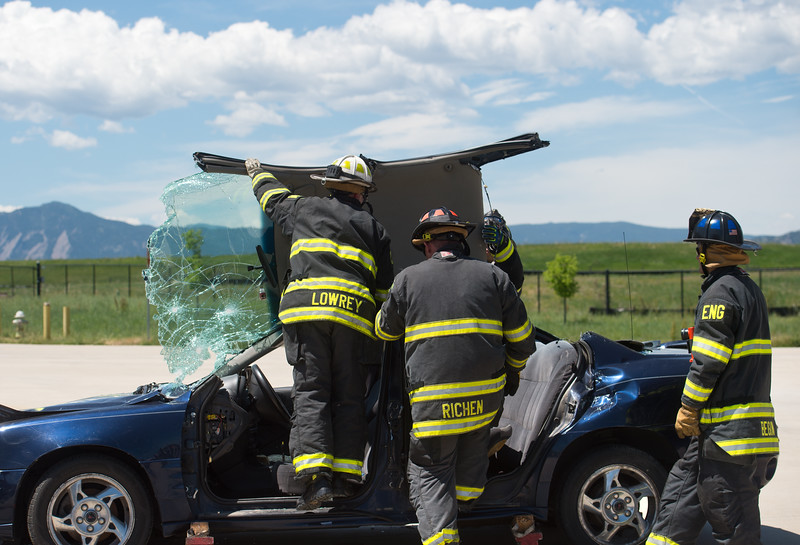 "From left to right, Chief Fire Marshal Dave Lowrey, Lieutenant Travis Richen and Engineer Dave Begin take the roof off a car as part of an extrication scenario during Camp Boulder Fire at the Boulder Wildland Fire Training Center on Thursday. The camp is intended to teach the children about what it takes to be a firefighter and engages them in team building exercises.<br /> More photos:  <a href=""http://www.dailycamera.com"">http://www.dailycamera.com</a><br /> (Autumn Parry/Staff Photographer)<br /> June 9, 2016"