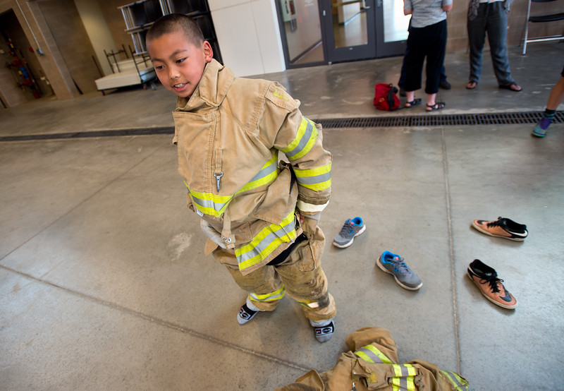 "Guanyu Hou, 11, from Creekside Elementary, puts on personal protective equipment during Camp Boulder Fire at the Boulder Wildland Fire Training Center on Thursday. The camp is intended to teach the children about what it takes to be a firefighter and engages them in team building exercises.<br /> More photos:  <a href=""http://www.dailycamera.com"">http://www.dailycamera.com</a><br /> (Autumn Parry/Staff Photographer)<br /> June 9, 2016"