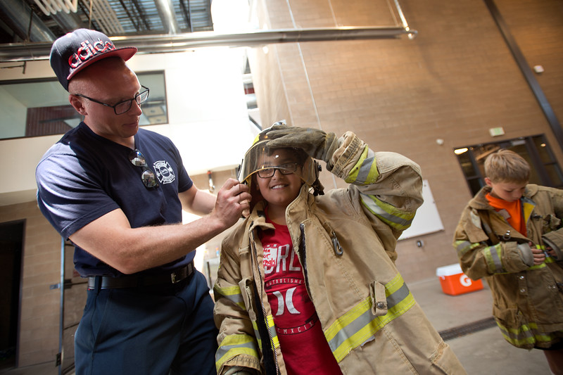 "Trevor Gappa, a life safety educator, helps Victor Gonzalez, 10, from Columbine Elementary, try on personal protective equipment during Camp Boulder Fire at the Boulder Wildland Fire Training Center on Thursday. The kids spent the day learning about what it takes to be a firefighter and participated in team building exercises.<br /> More photos:  <a href=""http://www.dailycamera.com"">http://www.dailycamera.com</a><br /> (Autumn Parry/Staff Photographer)<br /> June 9, 2016"