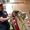 """Trevor Gappa, a life safety educator, helps Victor Gonzalez, 10, from Columbine Elementary, try on personal protective equipment during Camp Boulder Fire at the Boulder Wildland Fire Training Center on Thursday. The kids spent the day learning about what it takes to be a firefighter and participated in team building exercises.<br /> More photos:  <a href=""""http://www.dailycamera.com"""">http://www.dailycamera.com</a><br /> (Autumn Parry/Staff Photographer)<br /> June 9, 2016"""