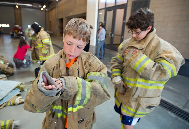 "Avery Nasta, 10, from Manhattan Middle School, tries on personal protective equipment during Camp Boulder Fire at the Boulder Wildland Fire Training Center on Thursday. <br /> More photos:  <a href=""http://www.dailycamera.com"">http://www.dailycamera.com</a><br /> (Autumn Parry/Staff Photographer)<br /> June 9, 2016"