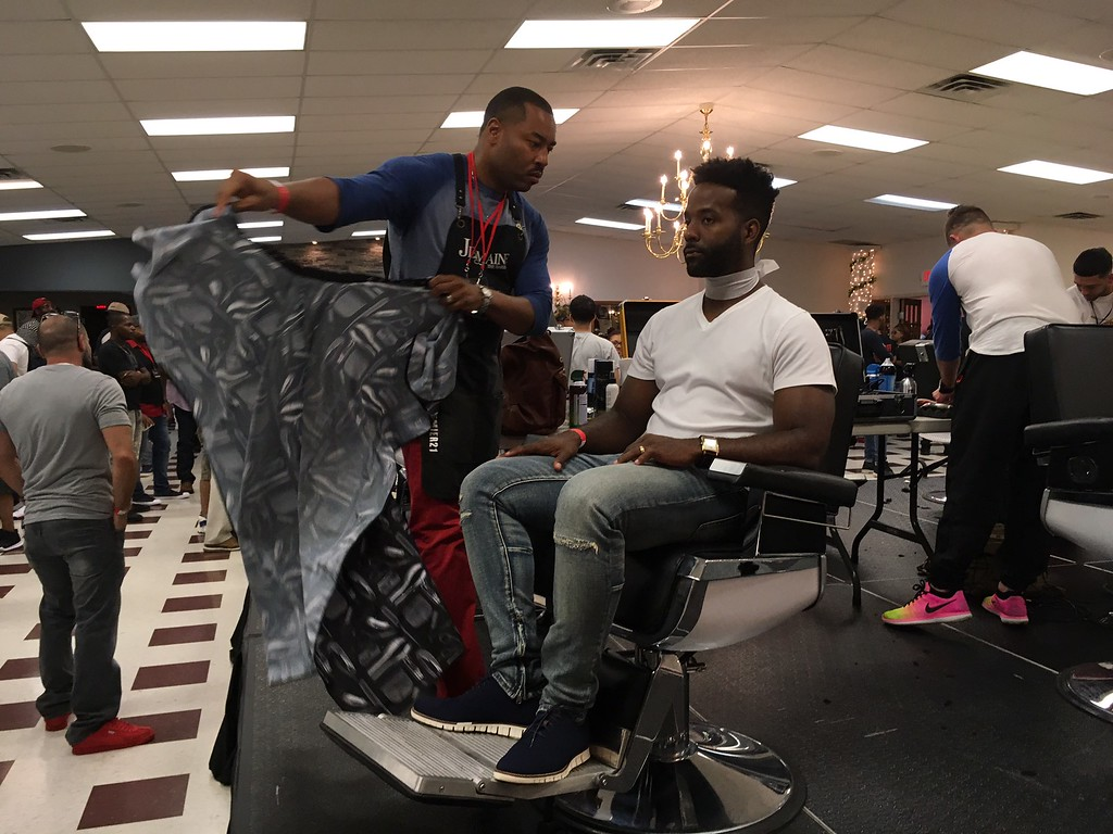 . Richard Payerchin - The Morning Journal <br> A competing barber gets ready to put his barber cloth over a model during the first Steel City Barber Expo held July 16, 2017, at Rosewood Place, 4493 Oberlin Ave., Lorain. Barbers battled for a championship belt in the event sponsored by La Fortaleza and Headlinerz Barbership.
