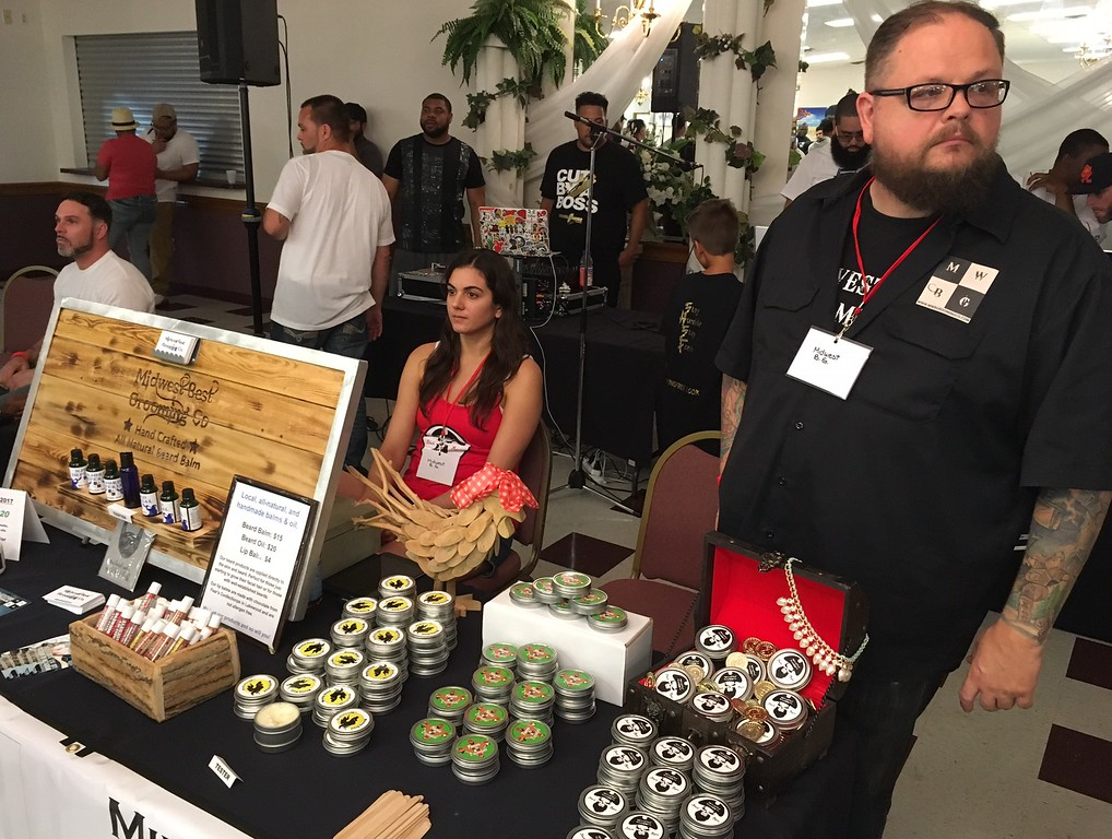 ". Richard Payerchin - The Morning Journal <br> Michelle Athanas, center, and Tim Novak, right, two of the four founders of Midwest Best Grooming Co., operate their booth at the first Steel City Barber Expo held July 16, 2017, at Rosewood Place, 4493 Oberlin Ave., Lorain. ""We want to change the world one beard at a time,\"" said Novak."