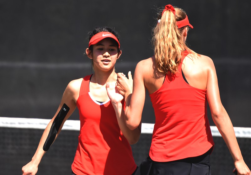 Fairview's Katie Hirasaki high-fives No. 1 doubles teammate Denali Pinto during the first day of the Class 5A girls tennis state championships on Thursday, May 10, at Gates Tennis Center in Denver.