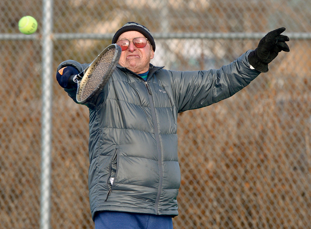 ". LONGMONT, CO - JANUARY 15: Dave Dreyfuss, 85, returns a serve while playing tennis in 25 degree weather January 15, 2019. ""We are the \'Hardy\' Boys out here,\"" Cathy Young said. The informal group of seniors meets Tuesday, Thursday, and Saturday mornings at Carr Park throughout the year, unless there\'s snow or ice on the courts. \""We always welcome new blood,\"" Bill Fairchild said. (Photo by Lewis Geyer/Staff Photographer)"