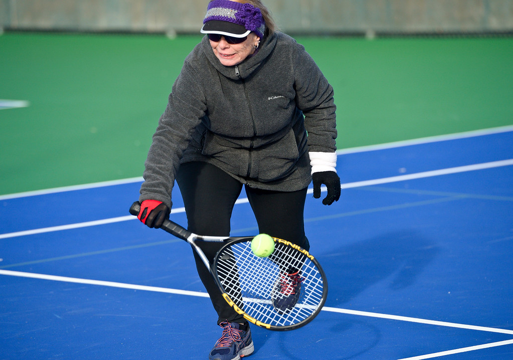 ". LONGMONT, CO - JANUARY 15: Jan DeBruin, 66, hits a return while playing tennis in 25 degree weather January 15, 2019. ""We are the \'Hardy\' Boys out here,\"" Cathy Young said. The informal group of seniors meets Tuesday, Thursday, and Saturday mornings at Carr Park throughout the year, unless there\'s snow or ice on the courts. \""We always welcome new blood,\"" Bill Fairchild said. (Photo by Lewis Geyer/Staff Photographer)"