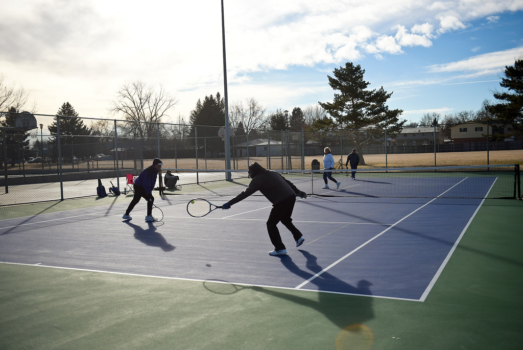 ". LONGMONT, CO - JANUARY 15: From left: Mark Handley, 68, Bill Fairchild, 89, Cathy Young, 65, and Dave Dreyfuss, 85 play tennis in 25 degree weather January 15, 2019. ""We are the \'Hardy\' Boys out here,\"" Cathy Young said. The informal group of seniors meets Tuesday, Thursday, and Saturday mornings at Carr Park throughout the year, unless there\'s snow or ice on the courts. \""We always welcome new blood,\"" Fairchild said.  (Photo by Lewis Geyer/Staff Photographer)"