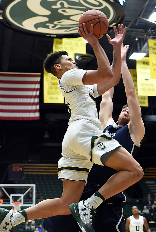 . Colorado State University\'s #15 Anthony Bonner goes up for a shot as Arkansas-Fort Smith\'s #10 Ognjen Vasiljevic tries to block during their game Tuesday, Dec. 6, 2016, at Moby Arena in Fort Collins. (Photo by Jenny Sparks/Loveland Reporter-Herald)