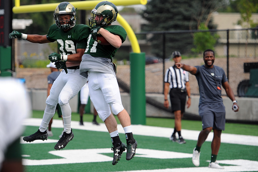. Wide receiver Thomas Pannunzio, left, chest bumps Anthony Grassi during practice Thursday, August 2, 2018 in Fort Collins, Colorado. (Sean Star/Loveland Reporter-Herald)