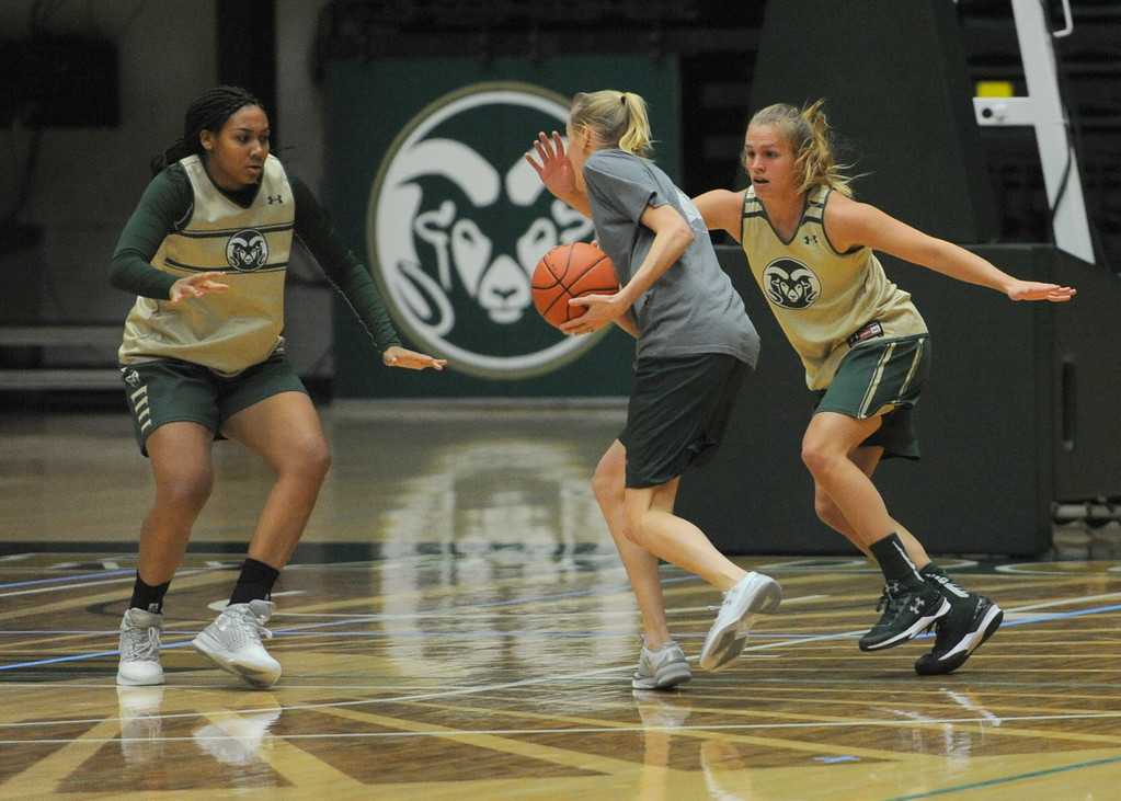. Colorado State\'s Liah Davis, left, and Callie Kaiser, right, defend coach Amber Cunningham during a practice at Moby Arena in Fort Collins.