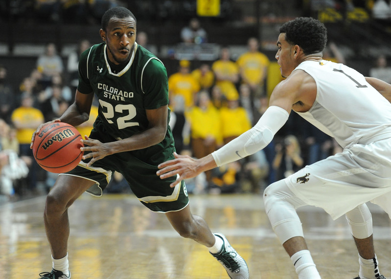 Colorado State's J.D. Paige (22) drives against Wyoming's Justin James at the Arena-Auditorium in Laramie, Wyoming, on Saturday. (Sean Star / Loveland Reporter-Herald)