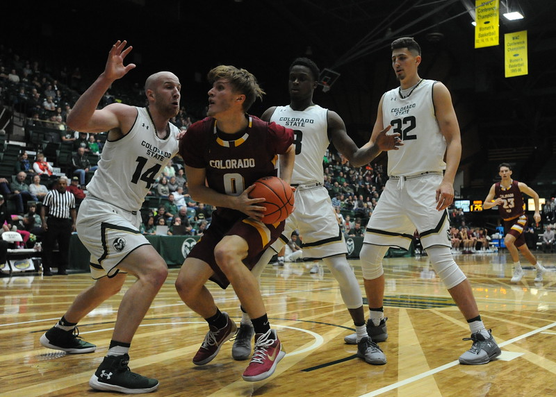 Colorado Mesa's Michael Skinner (0) is defended by Colorado State's Robbie Berwick (14), Raquan Mitchell (3) and Nico Carvacho (32) on Friday night at Moby Arena.