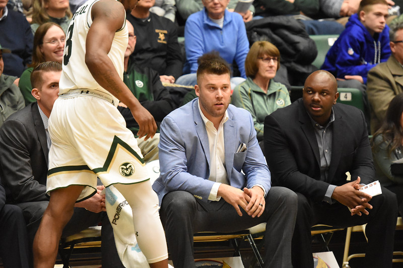 Colorado State interim coach Jase Herl, middle, sits next to assistant Willie Glover, right, as Raquan Mitchell gets set to check in during their game February 22, 2018 at Moby Arena in Fort Collins. (Sean Star / Loveland Reporter-Herald)