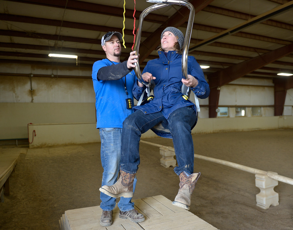 . Jesse Surratt, of Accessible Systems in Greeley, shows executive director Michele Bruhn how to use the new SureHands mechanical lift after it was installed Thursday at the Colorado Therapeutic Riding Center, 11968 Mineral Rd. The lift will be used to accommodate more people with disabilities and help them mount horses. To view a video and photos visit timescall.com. Lewis Geyer/Staff Photographer Feb. 15, 2018