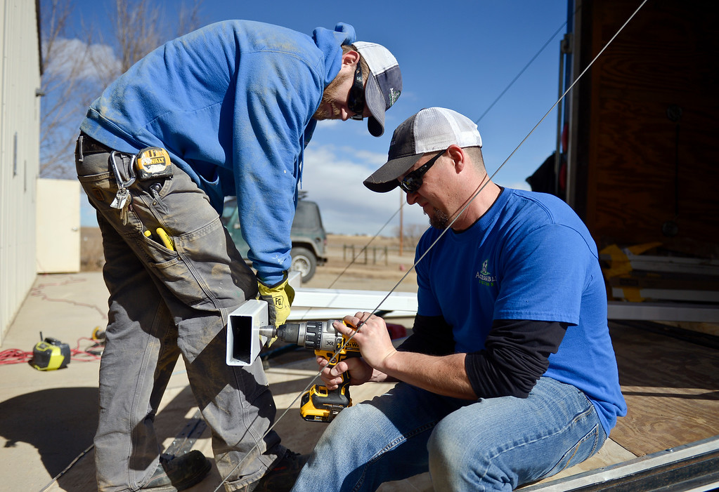 . Josh Whitaker, left, and Jesse Surratt, of Accessible Systems in Greeley, begin to install a SureHands mechanical lift Thursday at the Colorado Therapeutic Riding Center, 11968 Mineral Rd. The lift, donated by the family of Lib Matsch, will be used to accommodate more people with disabilities and help them mount horses. To view more photos and a video visit timescall.com. Lewis Geyer/Staff Photographer Feb. 15, 2018