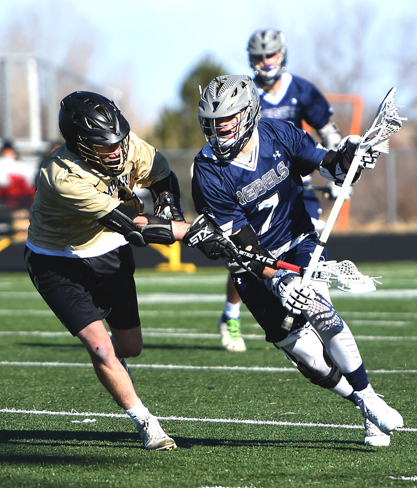 Monarch's Sean Bohling checks a Columbine attackman during the game between No. 8 Monarch and No. 4 Columbine on Friday, March 16, at Monarch High School.