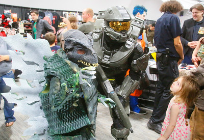 Richard Strobach of McKinleyville, aka Master Chief from Halo, and Rebel Damrow, 8, of Eureka, in a Godzilla costume his dad Forrest made, pose for a photo as Kira Moran, 4, of McKinleyville checks them out at ComicCon at the Blue Lake Casino on Saturday. (Shaun Walker -- The Times-Standard)