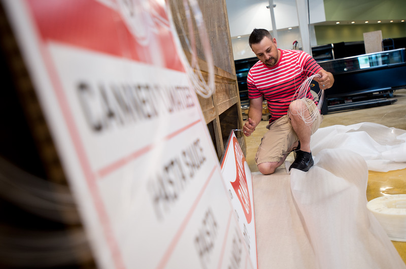 "Jason Lipnitzky, a production technician with Photo Craft, attaches wire to signs, which will be hung in the aisles of the new Lucky's Market on S. Broadway in Boulder on Wednesday. Lucky's Market is scheduled to open August 10th. <br /> More photos:  <a href=""http://www.dailycamera.com"">http://www.dailycamera.com</a><br /> (Autumn Parry/Staff Photographer)<br /> July 13, 2016"