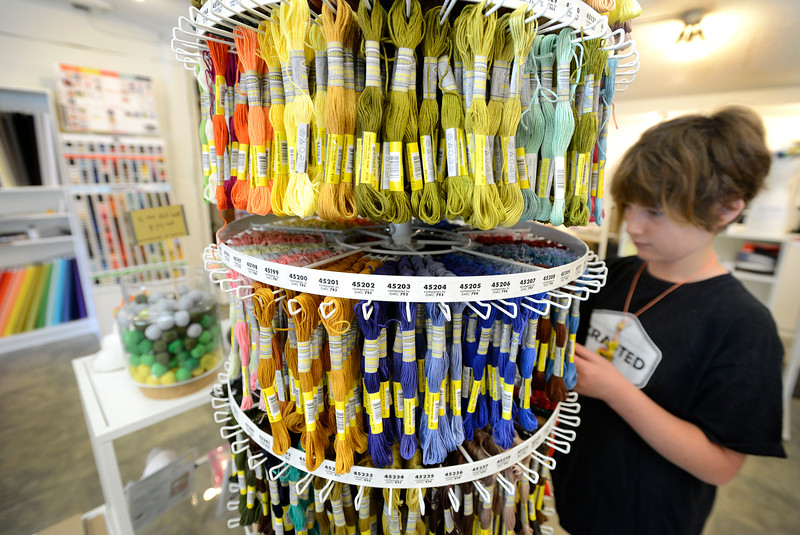 "Owyn Wyatt, 11, selects a piece of yarn from the display at Crafted Life in downtown Lafayette on Tuesday morning. For more photos go to  <a href=""http://www.dailycamera.com"">http://www.dailycamera.com</a><br /> <br /> Devi Chung For The Camera. June 14, 2016"