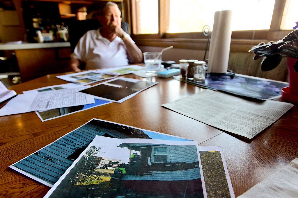 . Vernon Peppler, 88, sits at a table in his house off Colo. 66 in Longmont on Thursday surrounded by photos and police reports. The nearby house he grew up in was originally built around 1910 and had an additional 2 bedrooms added around 1947. It was struck by a car on April 27, 2017 but did not damage the foundation. Matthew Jonas/Staff Photographer May 11, 2017