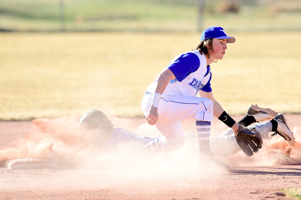. Dawson School\'s Seth Clemente (No. 2) waits for the throw as Peak to Peak High School\'s Matt Bagnato (No. 4) slides into second on Wednesday. More photos: BoCoPreps.com. Matthew Jonas/Staff Photographer March 15,  2017