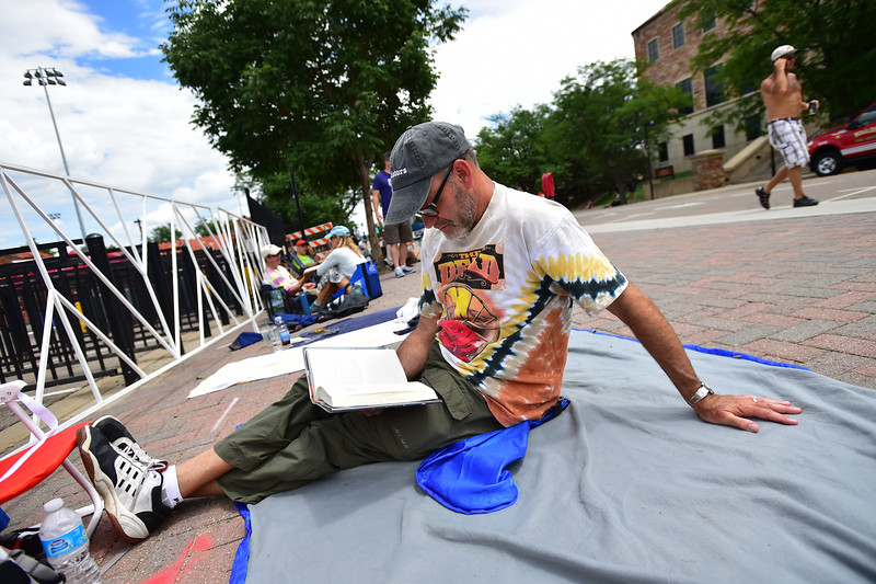 """Jack Lund reads a book while waiting outside Folsom Field for the Dead & Company concert in Boulder on Saturday.<br /> More photos:  <a href=""""http://www.dailycamera.com"""">http://www.dailycamera.com</a><br /> (Autumn Parry/Staff Photographer)<br /> July 2, 2016"""