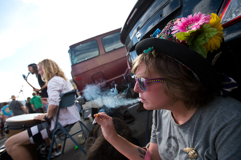 """Christina Dickinson smokes outside while listening to Curtis Thorniley and Kagen Morring play music near the University of Colorado's Folsom Field in Boulder on Sunday. Dickinson hopes to get a ticket to the Dead & Company concert.<br /> More photos:  <a href=""""http://www.dailycamera.com"""">http://www.dailycamera.com</a><br /> (Autumn Parry/Staff Photographer)<br /> July 3, 2016"""