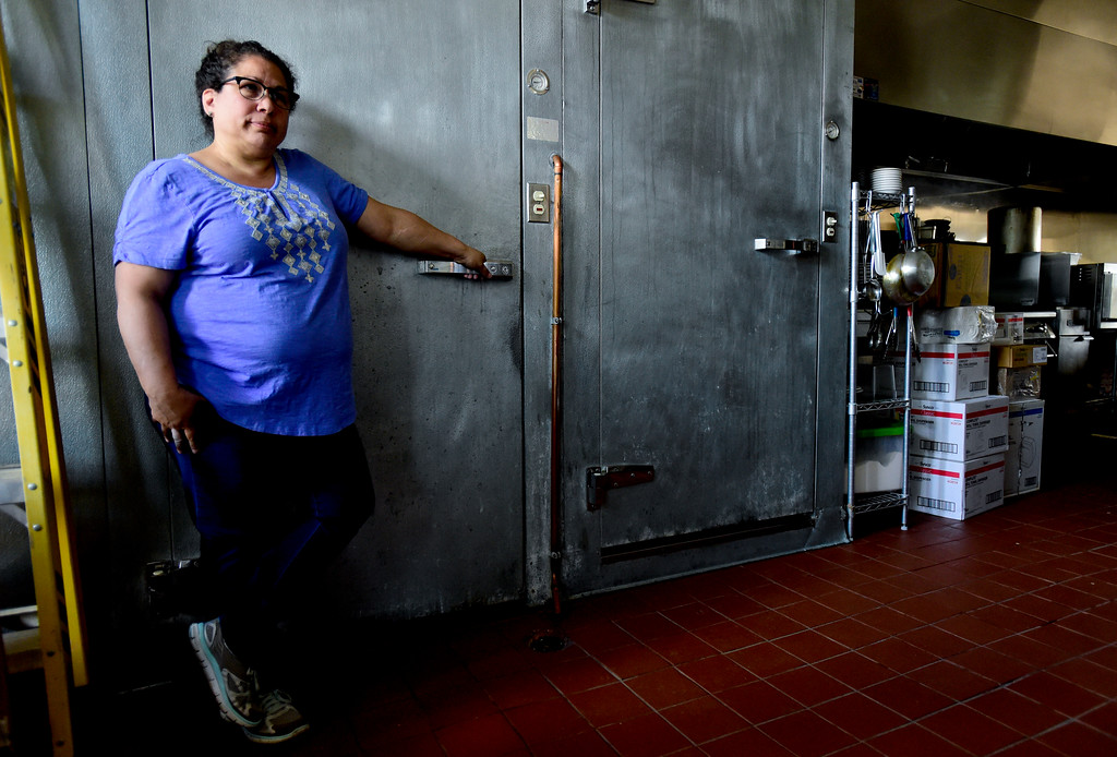 . Owner Zina Osborne stands in the dark kitchen next to the walk in coolers of her restaurant on Thursday morning after XCEL Energy mistakenly shut off the power at Deli-Cious Z\'s. After being open for less than two days, they had to close due to a utility billing error by XCEL. It will take at least another day to restock food and reopen to customers. More photos: DailyCamera.com. Matthew Jonas/Staff Photographer April 20,  2017