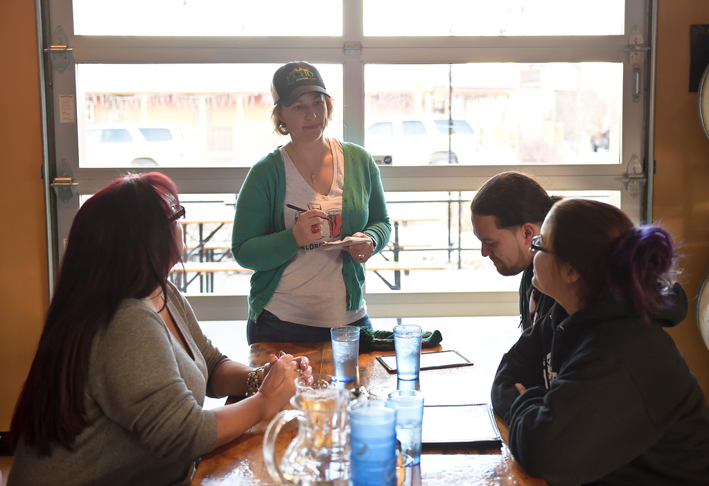 . Waitress Denise Jansson takes an order from Mirta Brito, left, and Darryn Rivera and Krystal Alonso at Echo Brewing Company in downtown Erie Friday evening. Lewis Geyer/Staff Photographer Dec. 22, 2017