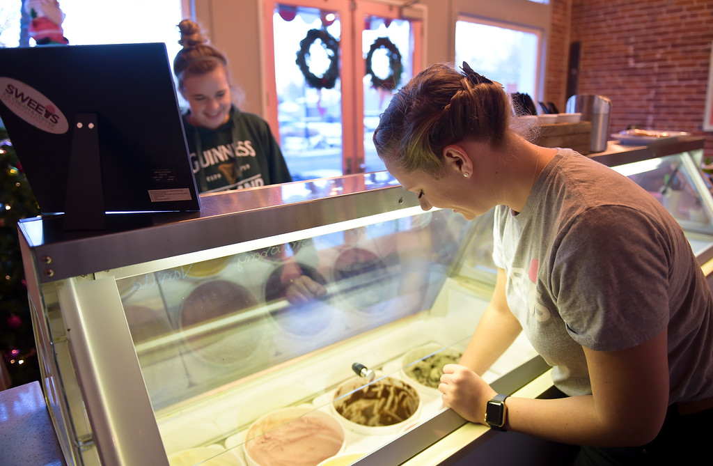 . Erin Moroze scoops ice cream for Riley Fischer at Sweets, 502 Briggs St., in downtown Erie Friday evening. Lewis Geyer/Staff Photographer Dec. 22, 2017