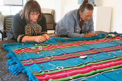 "Yurok Tribe members Susan Masten of Klamath, left, and Lavina Brooks of Crescent City sew community-donated earrings onto a blanket in the Native American Arts Goudi'ni Gallery at Humboldt State University on Thursday. The two and others are helping to add to the traveling Sing Our Rivers Red exhibit that is ""aimed at bringing awareness to the epidemic of missing and murdered indigenous women and colonial gender-based violence in the United States and Canada,"" the project's website states. For more information, go to singourriversred.wordpress.com. (Shaun Walker -- The Times-Standard)"