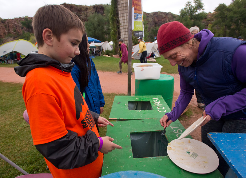 "Grant Gau, 12, from Lyons Middle/Senior High School, directs Dede de Percin where to dispose of compost and her reusable eco-plate during the Folks Fest in Lyons on Friday. Planet Bluegrass invested $15,000 in cutting edge eco-plates made from bamboo, sugar cane and corn, which are both compostable and reusable.<br /> More photos:  <a href=""http://www.dailycamera.com"">http://www.dailycamera.com</a><br /> (Autumn Parry/Staff Photographer)<br /> August 19, 2016"