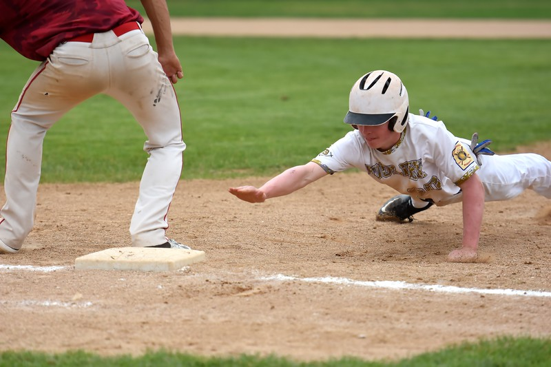 Boulder's Charlie Esson dives back into first to avoid getting picked off during the Panthers' Legion B state championship game against Elizabeth on Sunday at Machebeuf High School.