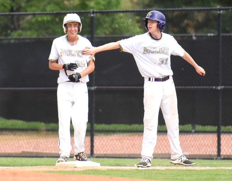 Boulder's Sean Coan is congratulated by teammate Travis Griffin after driving in a run during the Panthers' Legion B state championship game against Elizabeth on Sunday at Machebeuf High School.
