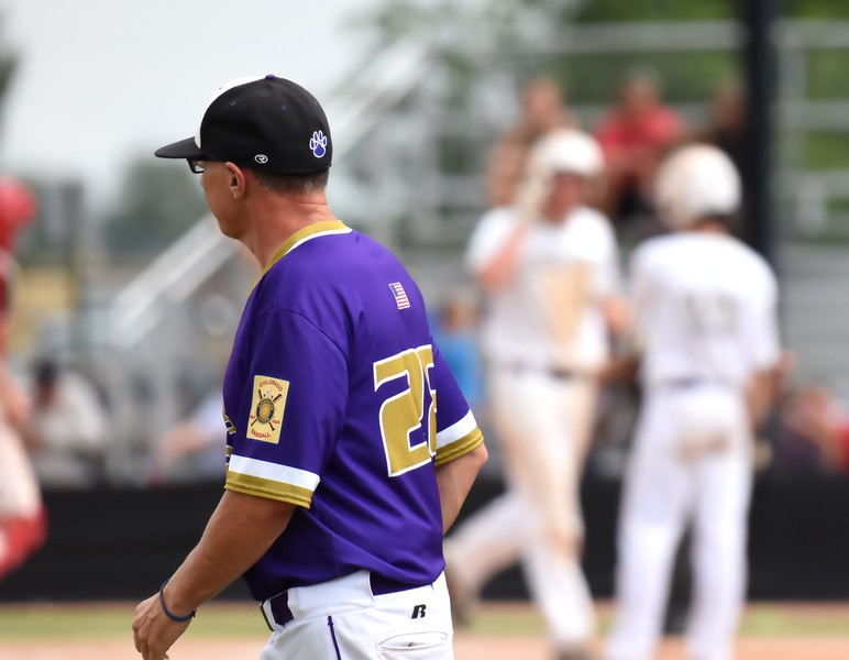 Boulder head coach Jack Taylor heads back to his post in the third-base coach's box while his players celebrate another run in the background during the Panthers' Legion B state championship game against Elizabeth on Sunday at Machebeuf High School.