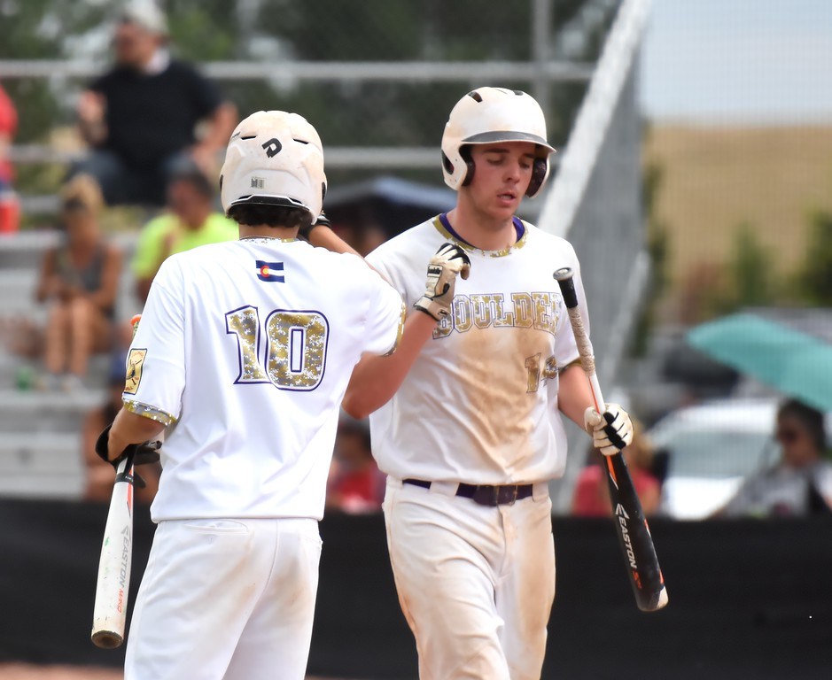 Boulder's Jackson Dinkel is congratulated by teammate Cai Lemieux-Mack after scoring a run during the Panthers' Legion B state championship game against Elizabeth on Sunday at Machebeuf High School.