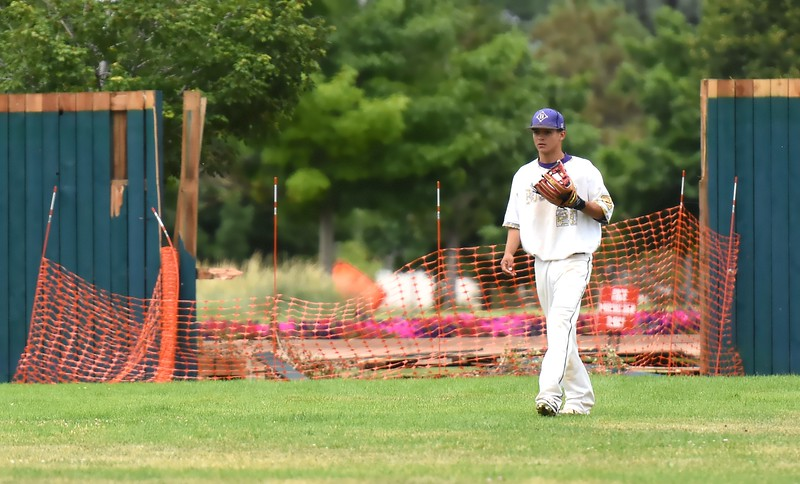Boulder centerfielder Tariq Maaherra readies for the next pitch during the Panthers' Legion B state championship game against Elizabeth on Sunday at Machebeuf High School, with the wreckage from when an alleged drunk driver crashed through the center-field wall on Thursday in the background.