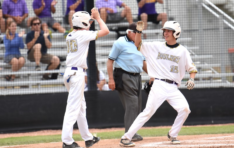 Boulder's Doug Blankenship is congratulated by teammate Charlie Esson after scoring a run during the Panthers' Legion B state championship game against Elizabeth on Sunday at Machebeuf High School.